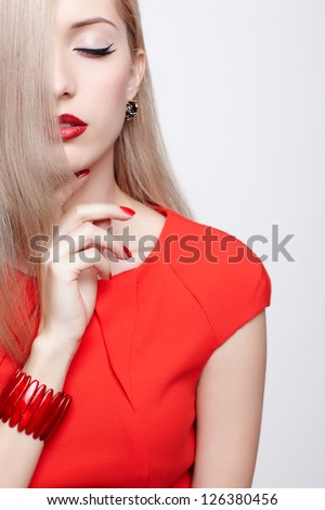 portrait of young beautiful long-haired blonde woman in red dress and bracelet with eyes closed and hair covering half of her face