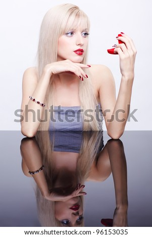 portrait of young beautiful long-haired blonde woman sitting at mirror table and  looking at red ring box - stock photo