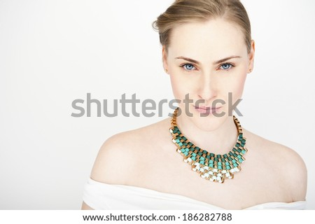 portrait of young beautiful long-haired blonde woman with necklace - stock photo