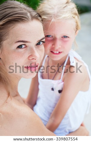 Portrait of Young Beautiful Mother Caring about Teenager Daughter. Look in the camera. Family, child, woman and happiness concept - stock photo