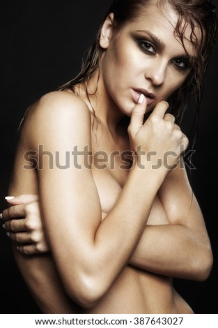 Portrait of young beautiful nude woman with wet shining  makeup  on black background