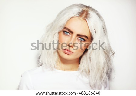 Portrait of young beautiful platinum blond woman with bold eyebrows