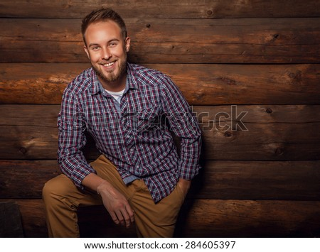 Portrait of young beautiful positive man against old wooden wall.