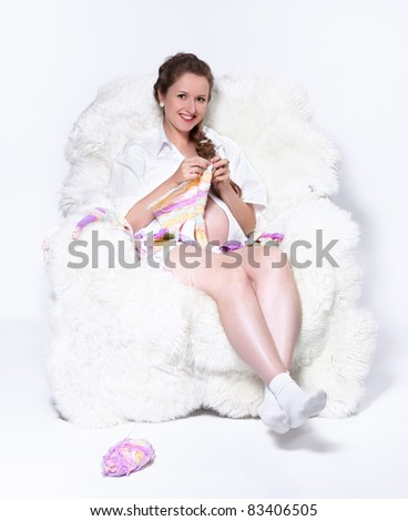 portrait of young beautiful pregnant woman in white furry arm-chair knitting baby's looses - stock photo