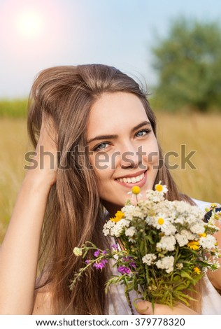 Portrait of young beautiful pretty cute romantic happy ukrainian woman wearing a wreath of wild flowers in summer day, outdoors. Series of photos  - stock photo