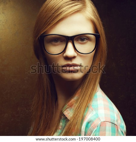 Portrait of young beautiful red-haired hipster girl wearing trendy glasses, casual shirt and posing over golden background. Close up. Studio shot - stock photo