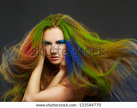 portrait of young beautiful red-haired woman posing on gray with waving hair colored with blue green and red - stock photo