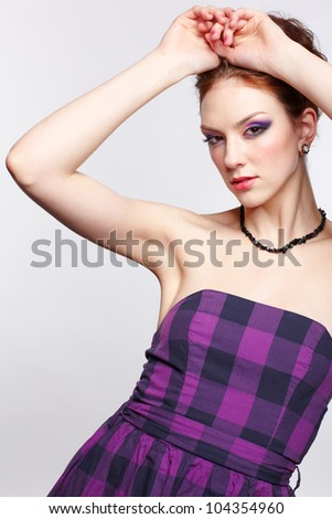 portrait of young beautiful red-haired woman putting hands over her head - stock photo