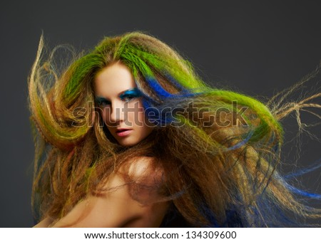 portrait of young beautiful redhead woman with long hair colored with blue green and red - stock photo