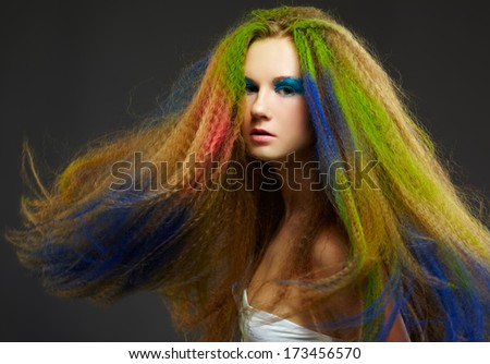 portrait of young beautiful redhead woman with long hair colored with green blue and red - stock photo