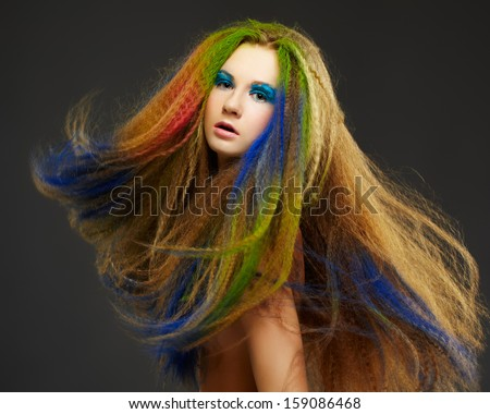portrait of young beautiful redhead woman with long hair colored with green red and blue