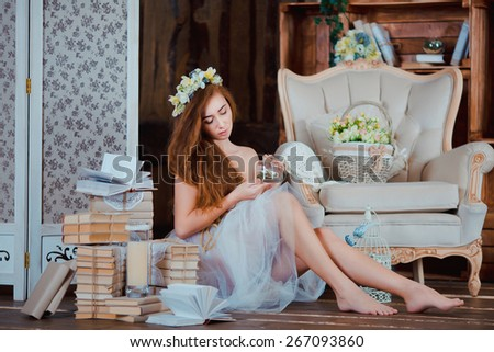 Portrait of young beautiful rude girl with flower wreath on her head in rustic wood interior - stock photo