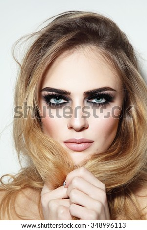 Portrait of young beautiful sexy blond girl with smoky eyes and long damaged hair
