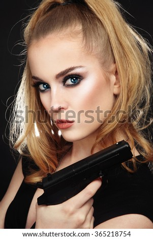 Portrait of young beautiful sexy blonde woman with stylish make-up holding a pistol in her hand - stock photo