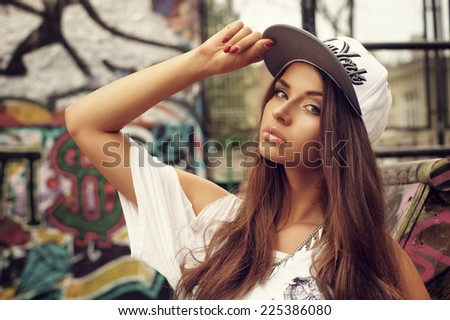 Portrait of young beautiful skater girl posing at city streets with graffiti. Fashion style portrait. - stock photo