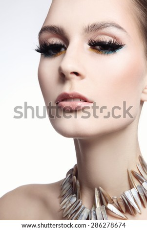 Portrait of young beautiful slim woman with false eyelashes and fancy necklace - stock photo