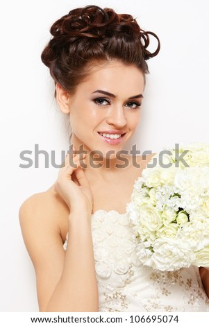 Portrait of young beautiful smiling bride with stylish make-up and hairdo over white wall - stock photo