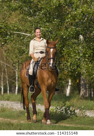 Portrait of young beautiful smiling brunette horsewoman in summer