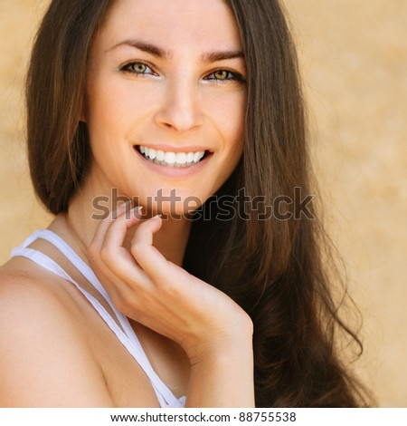 Portrait of young beautiful smiling brunette woman wearing white dress against yellow background.