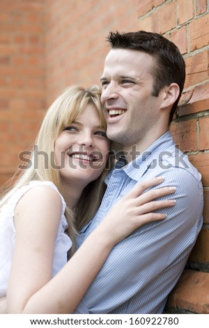 Portrait of young beautiful smiling caucasian couple leaning against brick building