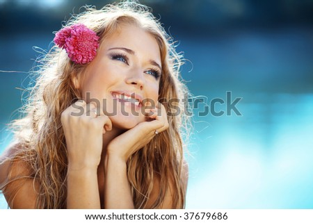 Portrait of young beautiful smiling female over blue lake water
