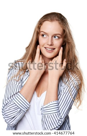 Portrait of young beautiful smiling girl touching her face looking to the side at blank copy space - stock photo