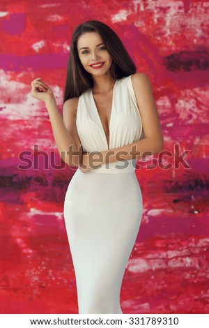 Portrait of young beautiful smiling girl wearing white evening dress with decollete, posing against stylish red background and ooking at you - stock photo