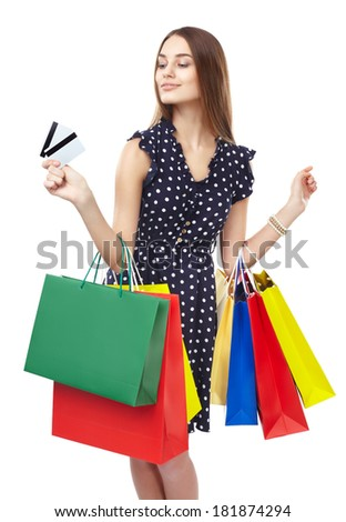 Portrait of young beautiful smiling happy woman with two credit cards and many colorful shopping bags pointing finger isolated on white background - stock photo