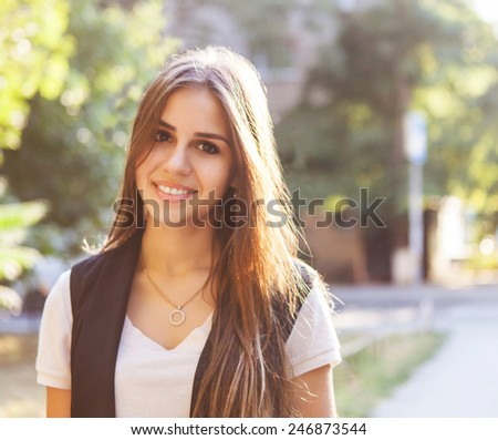 Portrait of young beautiful smiling teen girl against summer sunset