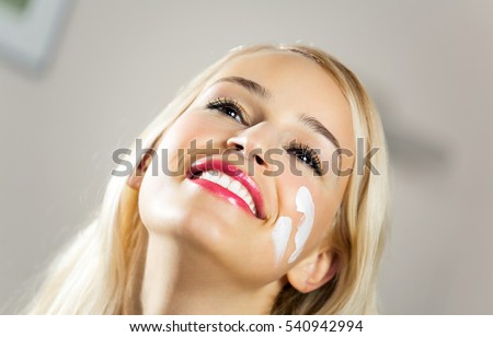 Portrait of young beautiful smiling woman applying creme at home. Scincare and beauty concept.