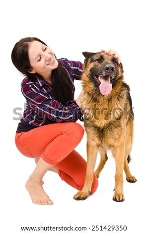 Portrait of young beautiful smiling woman sitting with a German Shepherd - stock photo