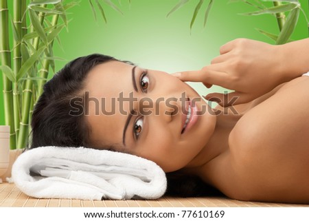Portrait of young beautiful spa woman lying on bamboo mat and smiling. Against green bamboo background. - stock photo