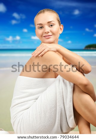 Portrait of young beautiful spa woman wearing white towel. Against blue sky background. - stock photo