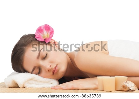 Portrait of young beautiful spa woman with closed eyes lying on bamboo mat at spa salon
