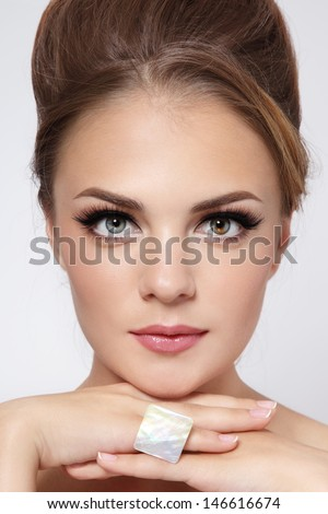 Portrait of young beautiful stylish girl with hair bun and trendy make-up - stock photo