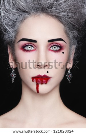 Portrait of young beautiful stylish gothic woman with vintage hairdo and bloody mouth - stock photo