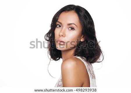 Portrait of young beautiful tan woman. Nude makeup. Dark eyes. White background. Isolated. Dark curly hair. Wearing white. Bride.