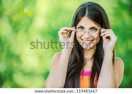 Portrait of young beautiful woman adjusts glasses and smiling, on green background summer nature.