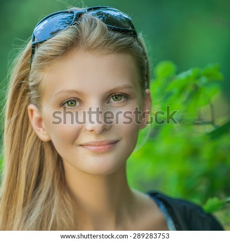 Portrait of young beautiful woman against summer garden.