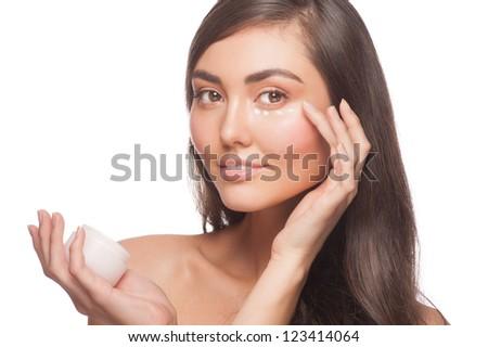 Portrait of young beautiful woman applying moisturizing cream. Isolated on white background - stock photo
