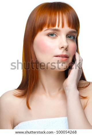 Portrait of young beautiful woman applying moisturizing cream on her face, isolated on white background