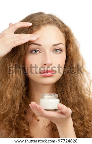 Portrait of young beautiful woman applying moisturizing cream on her face, isolated on white background - stock photo
