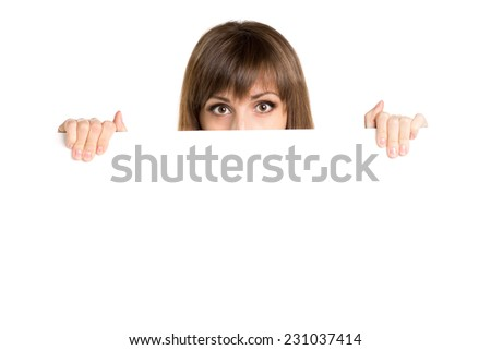 Portrait of young beautiful woman behind white blank board. Pretty girl holding paper card with copy space - stock photo