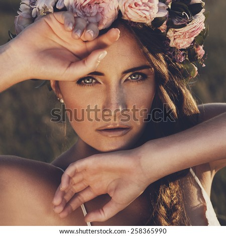 Portrait of young beautiful woman circlet of flowers on head outdoors - stock photo