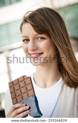 Portrait of young beautiful woman eating chocolate - lifestyle outdoor image - stock photo