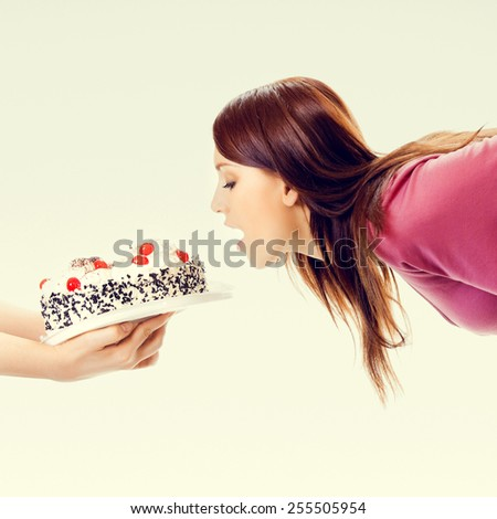 Portrait of young beautiful woman eating pie - stock photo