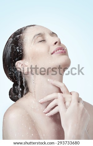 Portrait of young beautiful woman  getting splashed on blue background