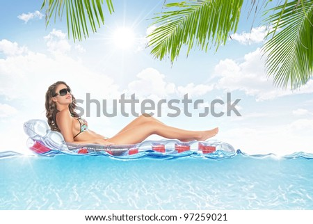 portrait of young beautiful woman hanging out on air mattress - stock photo