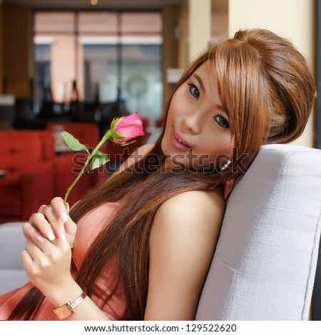 Portrait of young beautiful woman holding a red rose at the cafe.