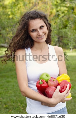 Portrait of young beautiful woman holding a vegetable on green background summer nature.